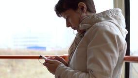 Une femme va en tram et écoute la musique sur des écouteurs sur un smartphone banque de vidéos