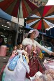 Une femme vendant des poupées de mode sur le marché de Chatuchak, Bangkok Image libre de droits
