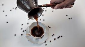 Une femme versant le caf? aromatique chaud dans une tasse ? une table blanche sur laquelle des grains de caf? sont dispers?s Caf? banque de vidéos