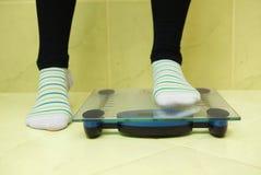 Une femme veut peser et se tient sur les échelles Photos stock