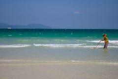 Une femme vietnamienne rassemble des coquilles de mer sur le rivage à Nha Trang, Vietnam Photographie stock libre de droits