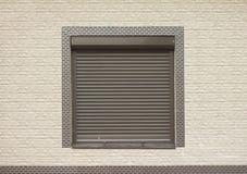 Une fenêtre avec les volets de roulement bruns Photographie stock libre de droits