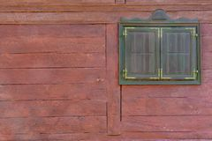Une fenêtre brune sur un mur en bois rouge de cabine photos libres de droits