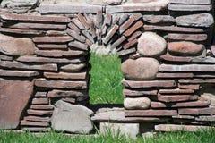 Une fenêtre dans un mur ornemental en pierre en parc de ville photographie stock