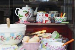 Une fenêtre de boutique avec des services à thé et d'autres ustensiles photographie stock libre de droits