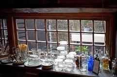 Une fenêtre de magasin d'antiquités de l'intérieur regardant  photos stock