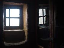 Une fenêtre en bois de vintage dans une chambre noire, du côté droit est une réflexion d'une fenêtre dans le verre Image libre de droits