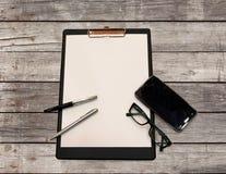 Une feuille blanche de papier avec un stylo et de smartphone sur une table en bois faite de conseil Photo stock
