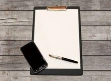 Une feuille blanche de papier avec un stylo et de smartphone sur une table en bois faite de conseil Photos stock