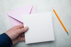 Une feuille carrée de livre blanc vide dans sa main, une enveloppe rose pour le courrier et un crayon jaune photographie stock libre de droits