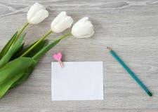 Une feuille de papier avec un stylo rouge et de mensonges de fleurs sur une table en bois blanche Laissez une note sur la table photographie stock libre de droits