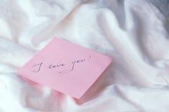 Une feuille de papier rose avec le ` de ` de mots je t'aime sur le blanc a chiffonné le tissu Images libres de droits