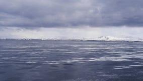 Une feuille lisse de l'eau froide d'océan avec les nuages foncés ci-dessus Photos stock