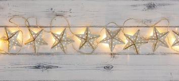 Une ficelle des lumières de Noël d'or d'étoile, sur le bois déstressé image stock