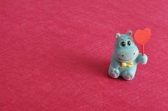 Une figurine d'hippopotame tenant un coeur rouge Photo libre de droits
