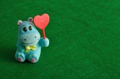 Une figurine d'hippopotame tenant un coeur rouge Image stock