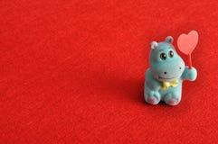 Une figurine d'hippopotame tenant un coeur rouge Images libres de droits