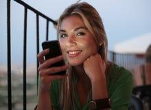 Une fille à l'aide du téléphone au restaurant Photos stock