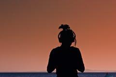 Une fille écoutant la musique par la mer Photo stock
