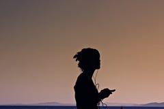 Une fille écoutant la musique par la mer Photographie stock libre de droits