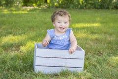 Une fille an adorable s'asseyant sur une caisse photographie stock