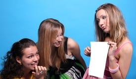 Une fille affichant à ses amis une liste de papier Photos stock