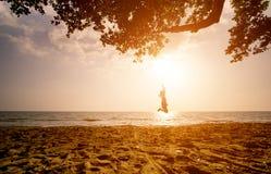 Une fille asiatique sautant sur la plage au temps de coucher du soleil Photographie stock libre de droits