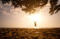 Une fille asiatique sautant sur la plage au temps de coucher du soleil Images stock