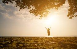 Une fille asiatique sautant sur la plage au temps de coucher du soleil Photo libre de droits