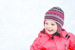 Une fille assez blanche dans un chapeau tricoté d'hiver et une salopette rose, souriant et riant dans la neige image stock