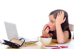 Une fille assez petite mange des fraises photographie stock