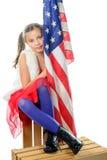 Une fille assez petite s'asseyant sur une boîte avec un drapeau américain photographie stock