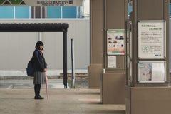 Une fille attend l'autobus Photos stock