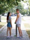 Une fille attirante à côté de son ami mignon avec un longboard sur un fond brouillé de parc Relations et amour Photographie stock libre de droits