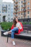 Une fille attirante avec de longs cheveux bruns et un sourire blanc de dent s'assied sur un banc et lui écrit des pensées sur le  Photographie stock libre de droits
