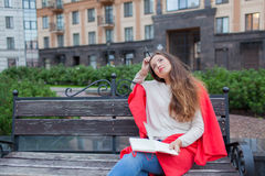 Une fille attirante avec de longs cheveux bruns s'assied sur un banc et lui écrit des pensées sur le fond de ville dans un carnet Photographie stock