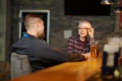 Une fille attirante, s'asseyant et parlant dans une barre avec un homme indoors Photo libre de droits