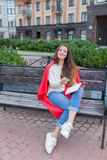Une fille attirante s'assied sur un banc et lui écrit des pensées sur le fond urbain dans un carnet rouge Elle utilise un chandai Photographie stock libre de droits
