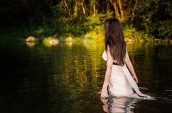 Une fille aux cheveux longs d'ajustement avec la robe blanche marchant par l'eau émouvante de rivière Image stock