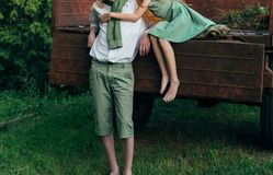 Une fille aux pieds nus dans une robe verte s'assied au dos d'une voiture et étreint a nu-pieds, à côté d'un type debout, un jour Photographie stock