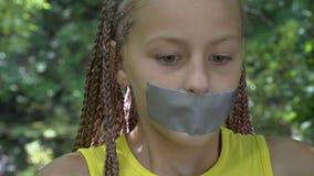 Une fille avec une bouche attachée du ruban adhésif banque de vidéos