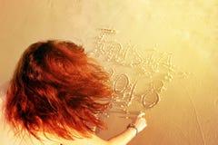 Une fille avec de beaux cheveux rouges lumineux écrit sur le bord de la mer dedans Images libres de droits