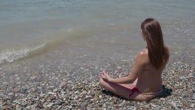 Une fille avec de longs cheveux débordants dans un maillot de bain s'assied sur la plage dans les vagues méditant dans une pose d banque de vidéos