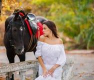 Une fille avec de longs cheveux et une longue robe blanche est tenante et regardante un cheval noir photos stock