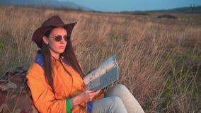 Une fille avec de longs cheveux fonc?s en gu?pe, chapeau de cowboy en cuir et verres s'assied, regardant la carte du voyageur s banque de vidéos