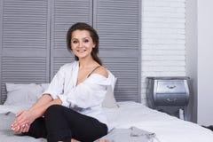 Une fille avec de longs cheveux s'est habillée dans des jeans noirs et une chemise blanche se reposant sur le lit Équipement occa photo libre de droits
