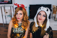 Une fille avec des andouillers et avec un chapeau de panda ensemble pendant une nouvelle année Images stock