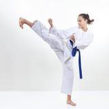 Une fille avec des battements bleus d'une ceinture donnent un coup de pied la jambe Image stock
