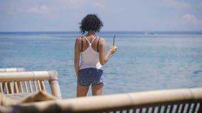 Une fille avec des cheveux courts, un T-shirt et le denim court-circuite des supports près du bord de la mer sur l'île de Bali El banque de vidéos