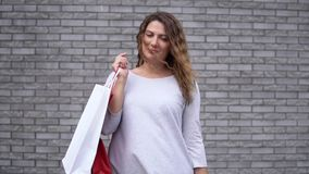 Une fille avec des paquets après l'achat avec une bonne humeur contre un mur des pierres Mouvement lent HD banque de vidéos
